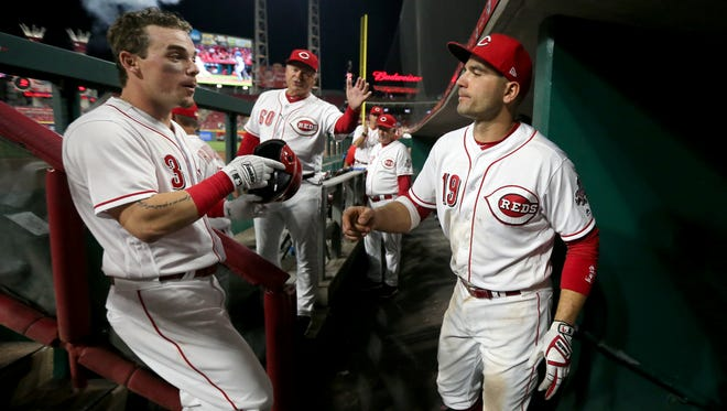 Cincinnati Reds second baseman Scooter Gennett (3) is congratulated by Cincinnati Reds first baseman Joey Votto (19) after hitting a two-run home run in the seventh inning during a National League baseball game between the New York Mets and the Cincinnati Reds, Tuesday, May 8, 2018, at Great American Ball Park in Cincinnati. Cincinnati won 7-2.