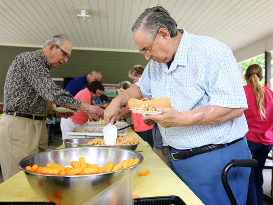 John Tompkins, of West Elmira, grabs a scoopful of Bugles Friday at a Meals on Wheels recognition event. Tompkins joined his brother who is a Meals on Wheels volunteer Friday at Grove Street Park in Elmira.