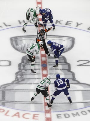 Players from the Dallas Stars and the Tampa Bay Lightning line up for the faceoff during first-period NHL Stanley Cup finals hockey action Saturday in Edmonton, Alberta.