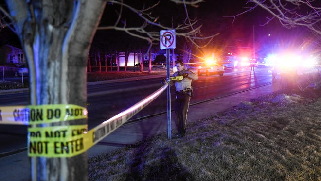 An officer strings crime scene tape near the scene a shooting Monday, March 20, on Waite Avenue North in Waite Park.