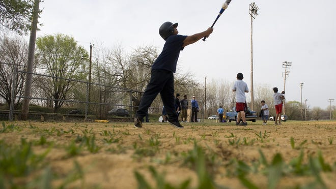 8-year-old Adrian Woloshin of Camden swings at a pitch as he trys out some of the donated baseball equipment that was delivered to the North Camden Little League at Pyne Poynt Park in Camden by Camden County employees on Friday afternoon. 03.23.12