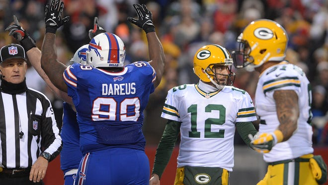 Green Bay Packers quarterback Aaron Rodgers (12) tries to find out what happened as two Bills defensive linemen celebrate the late fumble and safety that sealed the Packers loss against the Buffalo Bills at Ralph Wilson Stadium in Orchard Park, N.Y., December 14, 2014.