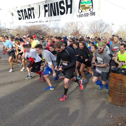 Runners take off at the starting line during the 11th