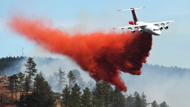 Fire crews fight a wildfire from the air in Sunshine Canyon on March 19, 2017, in Boulder, Colo.