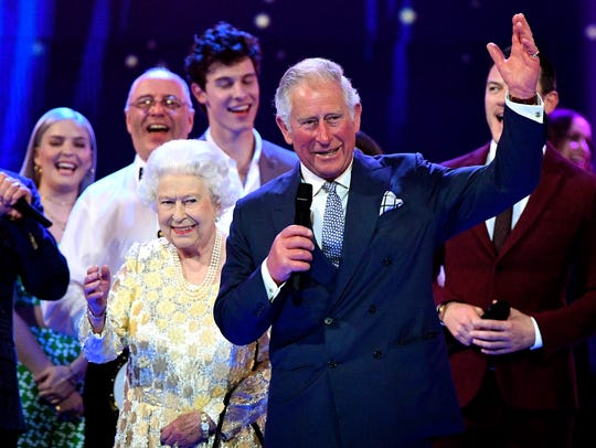 Queen Elizabeth II and Prince Charles stand with performers