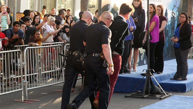 "The prankster journalist is forced off the red carpet in handcuffs after allegedly attacking Brad Pitt at the world premiere of ""Maleficent"" in Los Angeles."