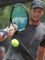 Zachary Northey returns the ball Sunday to Benjamin Mullis in the men's open singles during the 2015 Asfora/Clayton SD Adult Open championships at McKennan Park.