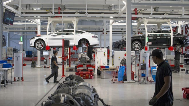 Tesla Model S automobiles stand on raised cradles during driving unit and rear axle fitting on the final assembly line at the Tesla Motors Inc. factory in Tilburg, Netherlands, on Oct. 8. After losing $1.88 billion since 2007, Tesla is piling on the personnel as it offers more models, builds the world's biggest battery factory and expands globally, including stores opening in Mexico City and Edinburgh.