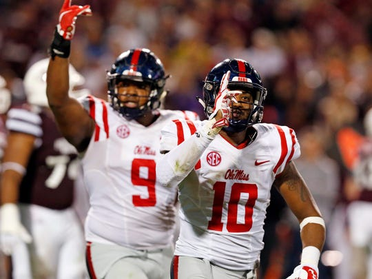 Ole Miss linebacker C.J. Johnson, right, and defensive tackle Breeland Speaks celebrate a play in the Egg Bowl on Saturday. Ole Miss won 38-27 against Mississippi State.