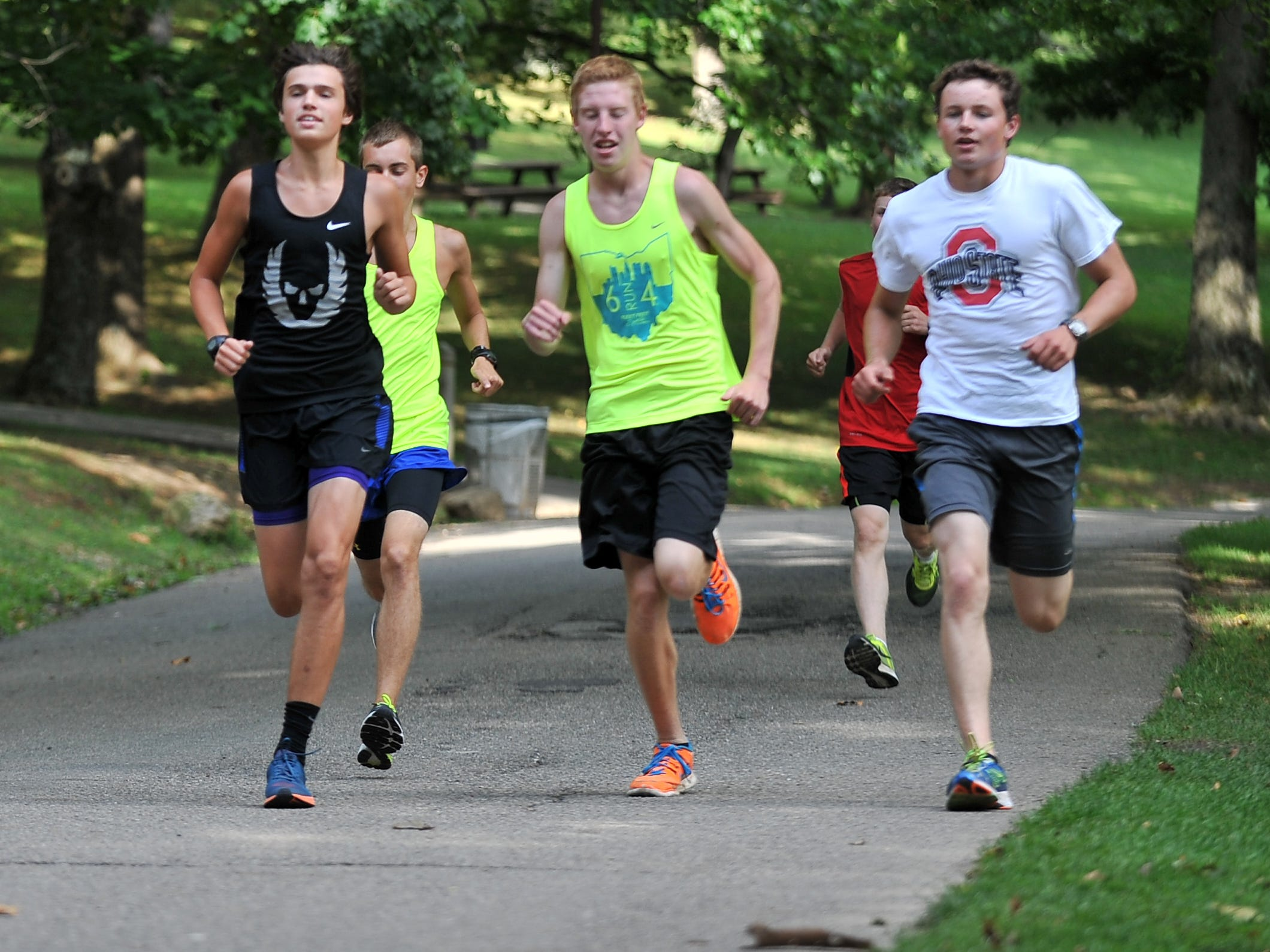 Jacob Thompson, left, Noah Davis, center, and Eric Hoover run Aug. 12 at Rising Park in Lancaster during Fairfield Christian Academy's cross country practice.