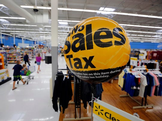 Signs and balloons remind shoppers of the sales tax