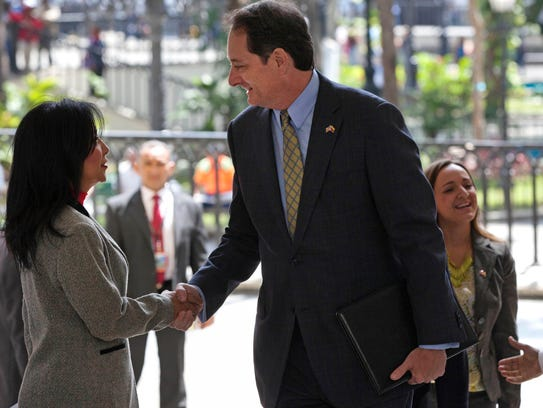 U.S. Charge d'Affaires Lee McClenny shakes hands with