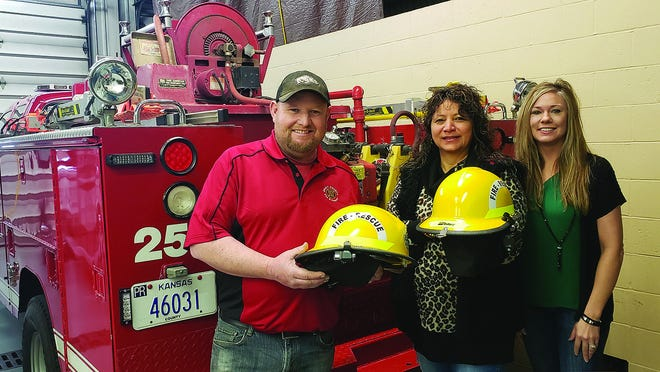 Lieutenant BJ Hayes of the Pratt County Fire and Rescue show fire helmet improvements made possible by a sizeable donation from the Pratt Elks Lodge. He is joined by Elks House Committee member Sara Ibarra, and Five-Year Trustee Kasey Voss.
