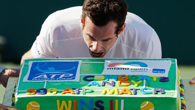 Andy Murray pretends to take a bite of a cake presented to him after his 500th ATP win after defeating Kevin Anderson on day nine of the Miami Open.