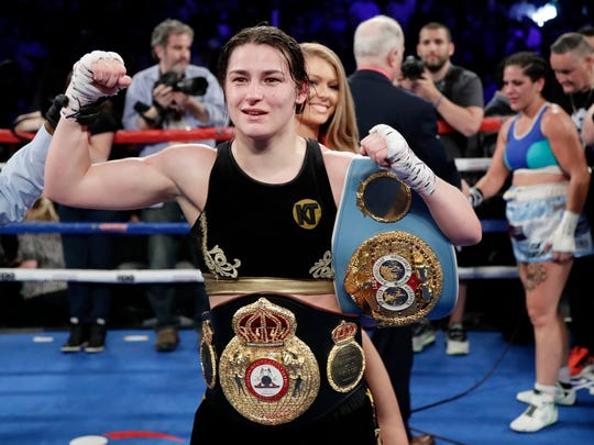 Ireland's Katie Taylor poses for photographs after winning a women's lightweight championship boxing match against Argentina's Victoria Noelia Bustos, back right, Saturday, April 28, 2018, in New York.