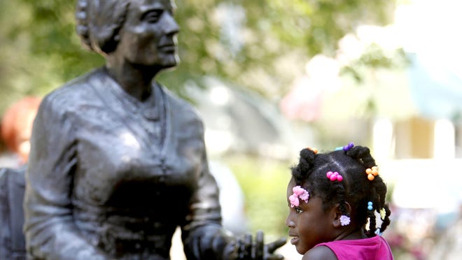 Katie Derby, 5, of Brighton poses for a picture next to the statue of Susan B. Anthony during the the festival commemorating her. (August 2011 file photo)