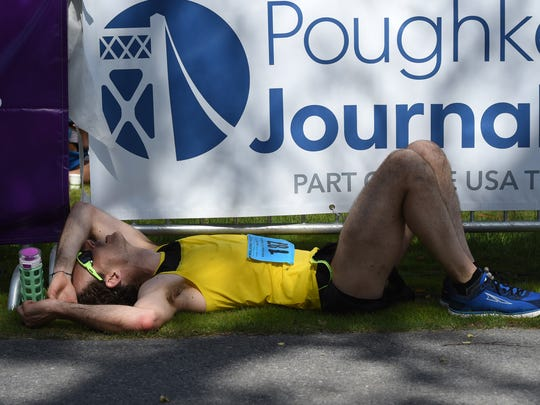 Adam Rau of Rocky Point collapses right after the finish line during the 2017 Walkway Marathon.