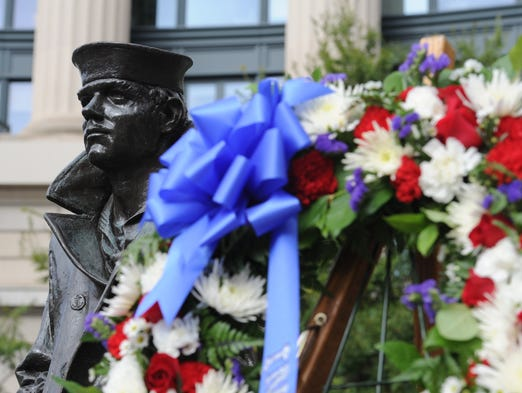 A wreath placed by Secretary of Defense Chuck Hagel stands next to a statue of a sailor at the Navy Memorial in memory of victims of the Sept. 16, 2013, shootings at the Washington Navy Yard.