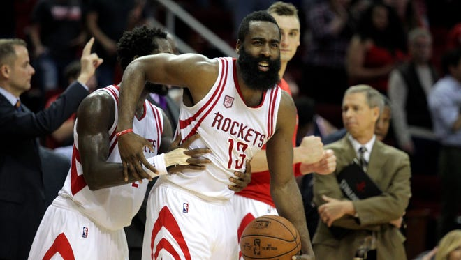 Houston Rockets guard James Harden (13) is embraced from behind by Houston Rockets guard Patrick Beverley (2) following Houston's 121-114 victory against the Charlotte Hornets at Toyota Center.