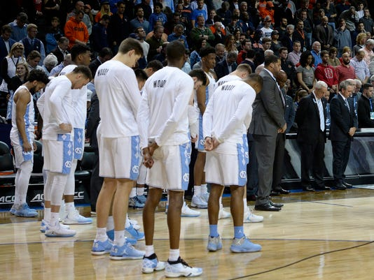 North Carolina team members and fans stand for a moment of silence to honor former UNC radio announcer Woody Durham, who died earlier this week, before the team's NCAA college basketball game against Syracuse in the second round of the Atlantic Coast Conference men's tournament Wednesday, March 7, 2018. in New York. (Chuck Liddy/The News & Observer via AP)