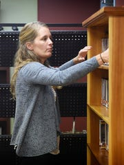 Richland Community Library Director Amy Davis [stocks shelves] on Sept. 27, 2016. Davis said costs are rising and the library is still depending on local government funding.