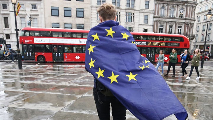 A demonstrator wrapped in a European flag leaves an