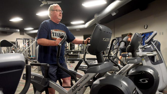Trevor Jackson does cardio on an elliptical machine at Great Life Fitness Club in Hartford on Thursday.