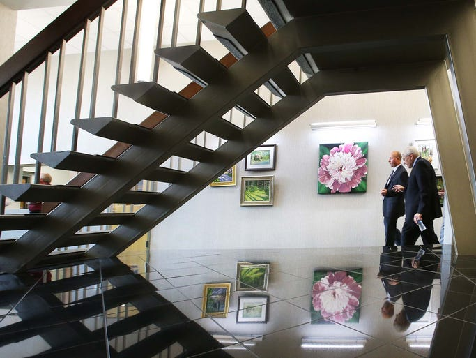 Visitors to the new city hall walk past art from the Southside Art League that hangs in the lobby. A ribbon-cutting ceremony and open house officially opened the new $6 million Greenwood City Center at 308 S. Madison Ave. Thursday, Aug. 7, 2014.