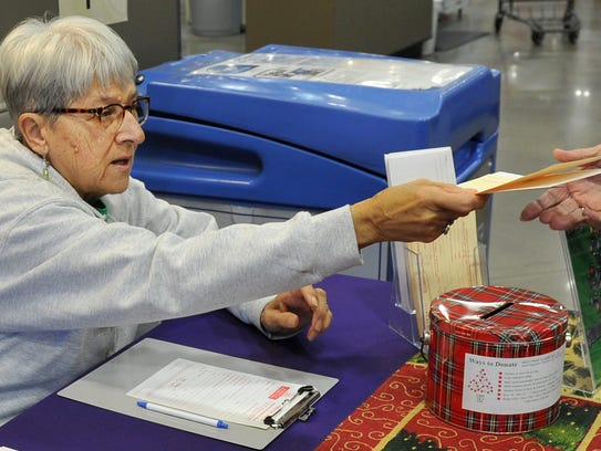 Hospice of Wichita Falls volunteer Shirley Visintainer hands out donation forms on Nov. 29 at Market Street.