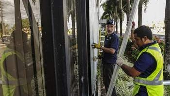 In this Oct. 4, 2014, file photo, maintenance workers Chris George, right, and Lawrence Borja install storm shutters at the International Trade Center Tamuning
