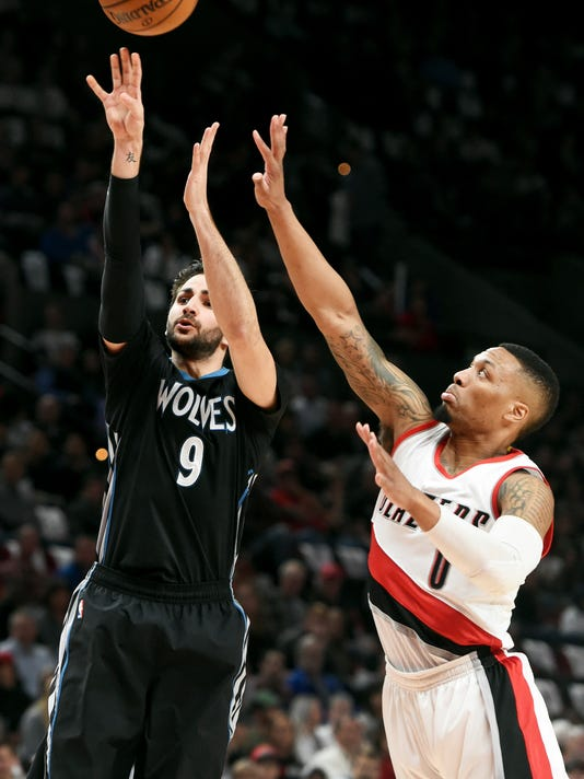 Minnesota Timberwolves guard Ricky Rubio hits a shot over Portland Trail Blazers guard Damian Lillard during the first half of an NBA basketball game in Portland, Ore., Thursday, April 6, 2017. (AP Photo/Steve Dykes)