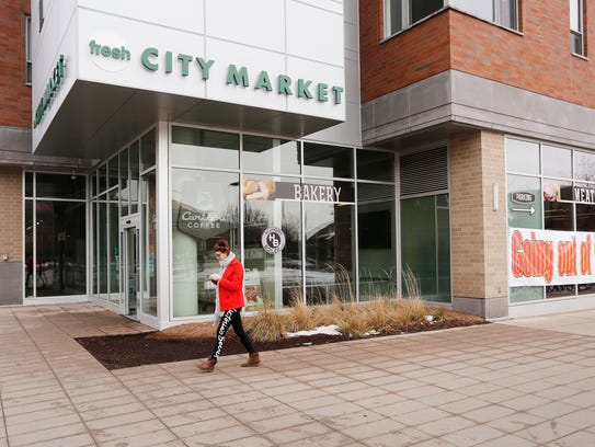 A woman passes the front door of Fresh City Market