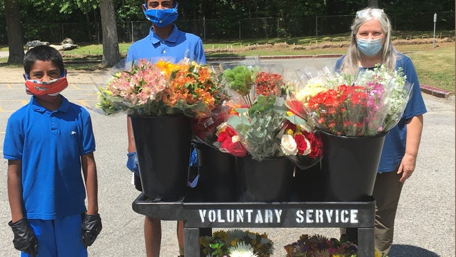 From left, brothers Sreewas  and Sreeman Lakshmanan, pause for a photo with Laurel Holland, voluntary service chief, at the Veterans Administration Hospital in Bedford, with flowers the brothers have donated.