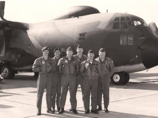 James Lawrence stands center in front of a AC-130.