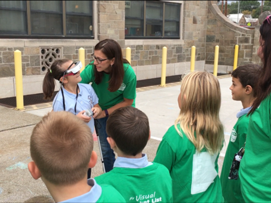 Remington Hedrick, 8, a second grader at St. Peter's, gets some help from her mother Amber as she wears new eSight 3 glasses and sees her classmates better for the first time Thursday morning.