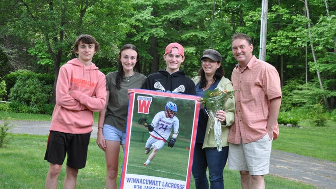 WHS senior Jacob Murray poses for a photo with his family after getting a surprise visit from his lacrosse teammates and coaches.