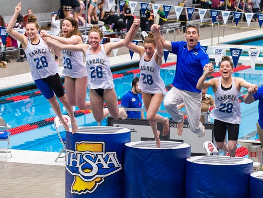 Chris Plumb, head coach of Carmel High School, is flanked by some of the Carmel swimmers as they jump from the victory podium into the diving well to celebrate winning the 2013-14 IHSAA Girls Swimming and Diving State Championships Saturday, Feb. 15, 2014, at Indiana University Natatorium in Indianapolis. Carmel High School won their 28th State Championship title.