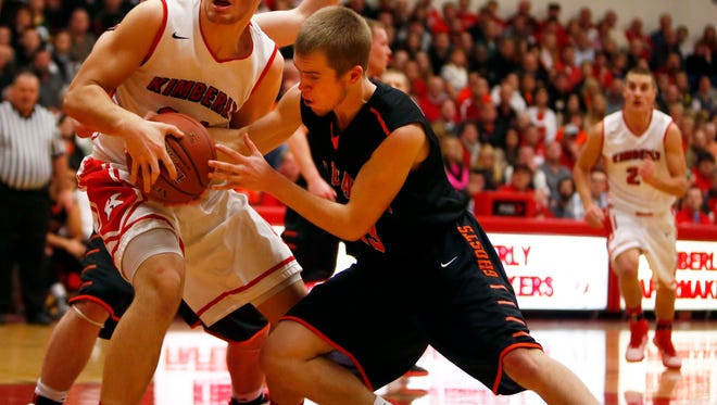 Carter Belling of Kaukauna (right) tries for a steal while defending Kimberly's Jordan Janssen during a Fox Valley Association boys' basketball game at Kimberly High School on Jan. 16.