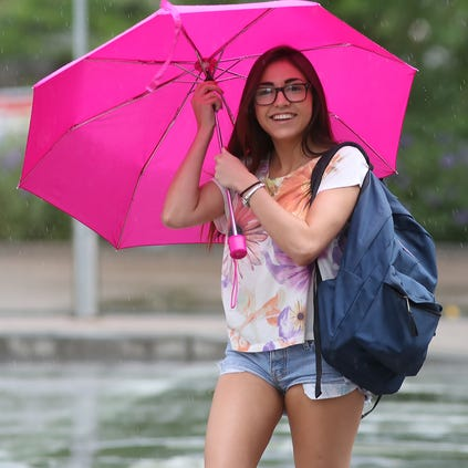 ASU Student Ali Goodale makes it across First Street in downtown Phoenix as the afternoon rain begins to fall.