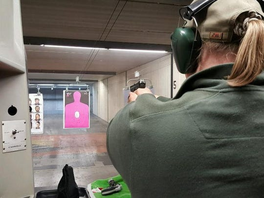 Kristin Sadler practices shooting her pistol at a gun