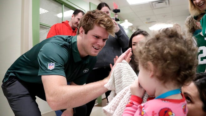 New York Jets quarterback Sam Darnold, left, who was drafted No. 3 overall in Thursday's NFL football draft, gives a high five to Sydney Kaplan, 3, of Mahwah, N.J., during a visit to the Goryeb Children's Hospital, Saturday, April 28, 2018, in Morristown, N.J.