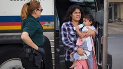 A woman carries a baby as immigrants are dropped off