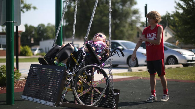 Andrea Capaldo, 7, gets a push from her older brother, Sal, 11, on a wheelchair-accessible swing at the Grimes Community Complex on Thursday, Aug. 13, 2015.