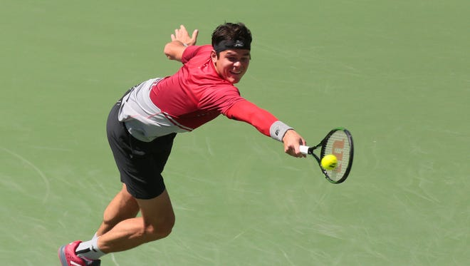 Milos Raonic of Canada returns the ball to David Goffin, of Belgium during the men's semifinals at the BNP Paribas Open on Saturday.