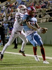 Hirschi's Javen Banks holds the ball out as he runs