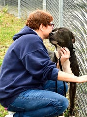 Chaos the dog receives a kiss from a Humane Society of St. Lucie volunteer in this file photo.