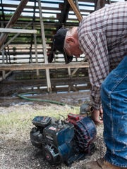 Ben Arps unhooks a pump at the Augusta Rodeo Grounds during cleanup efforts last month.