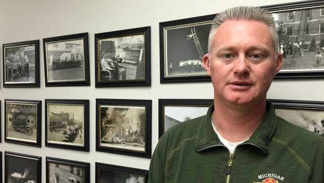 Lansing firefighter Eric Weber poses in front of a wall of historic photos of firefighters at the Lansing firefighter union offices in downtown Lansing on March 22, 2016. Weber helped push for the Legislature to create a firefighter cancer fund.