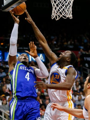 Atlanta Hawks forward Paul Millsap (4) shoots the ball over Golden State Warriors forward Draymond Green (23) go up for a rebound in the third quarter at Philips Arena.
