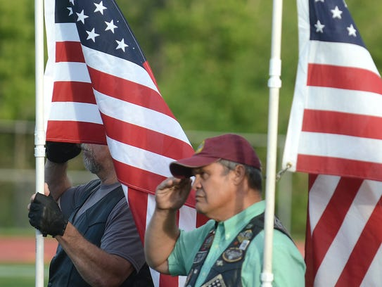 A pair of veterans salute the American Flag during